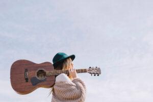 kobieta-niosąca-gitarę-kurs-gitarowy
